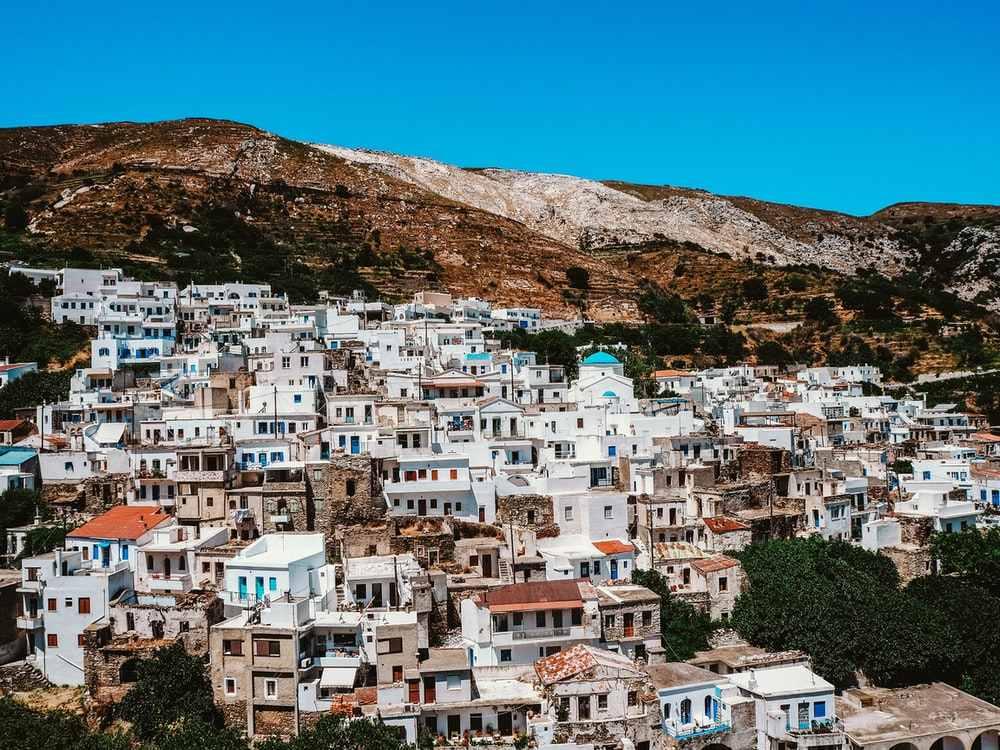 white and brown concrete houses near brown mountain under blue sky during daytime