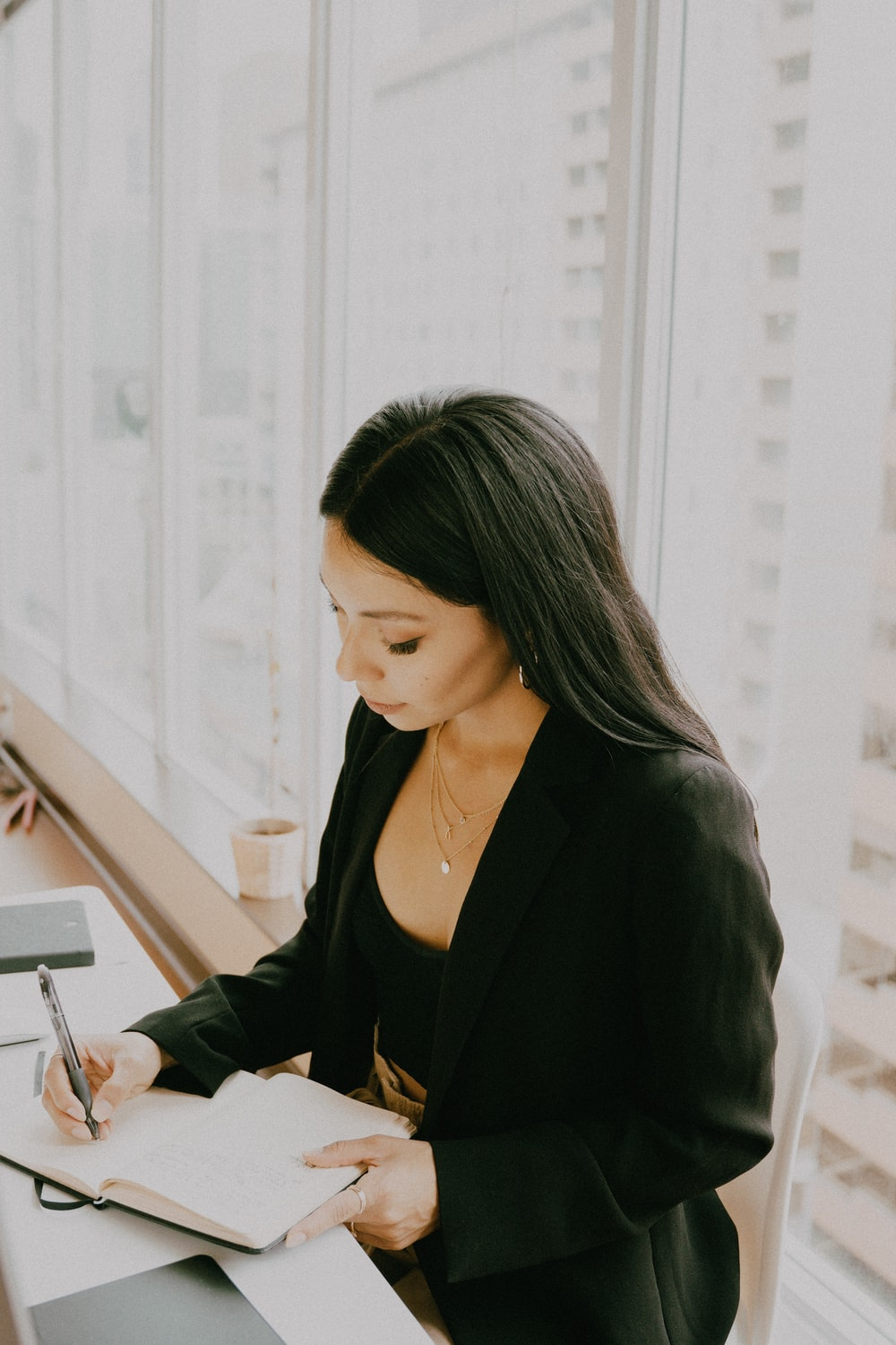 woman in black blazer using white tablet computer