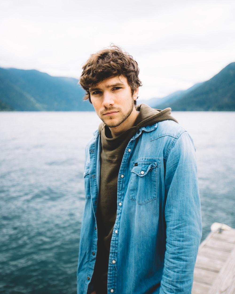 man in blue denim jacket standing near body of water during daytime