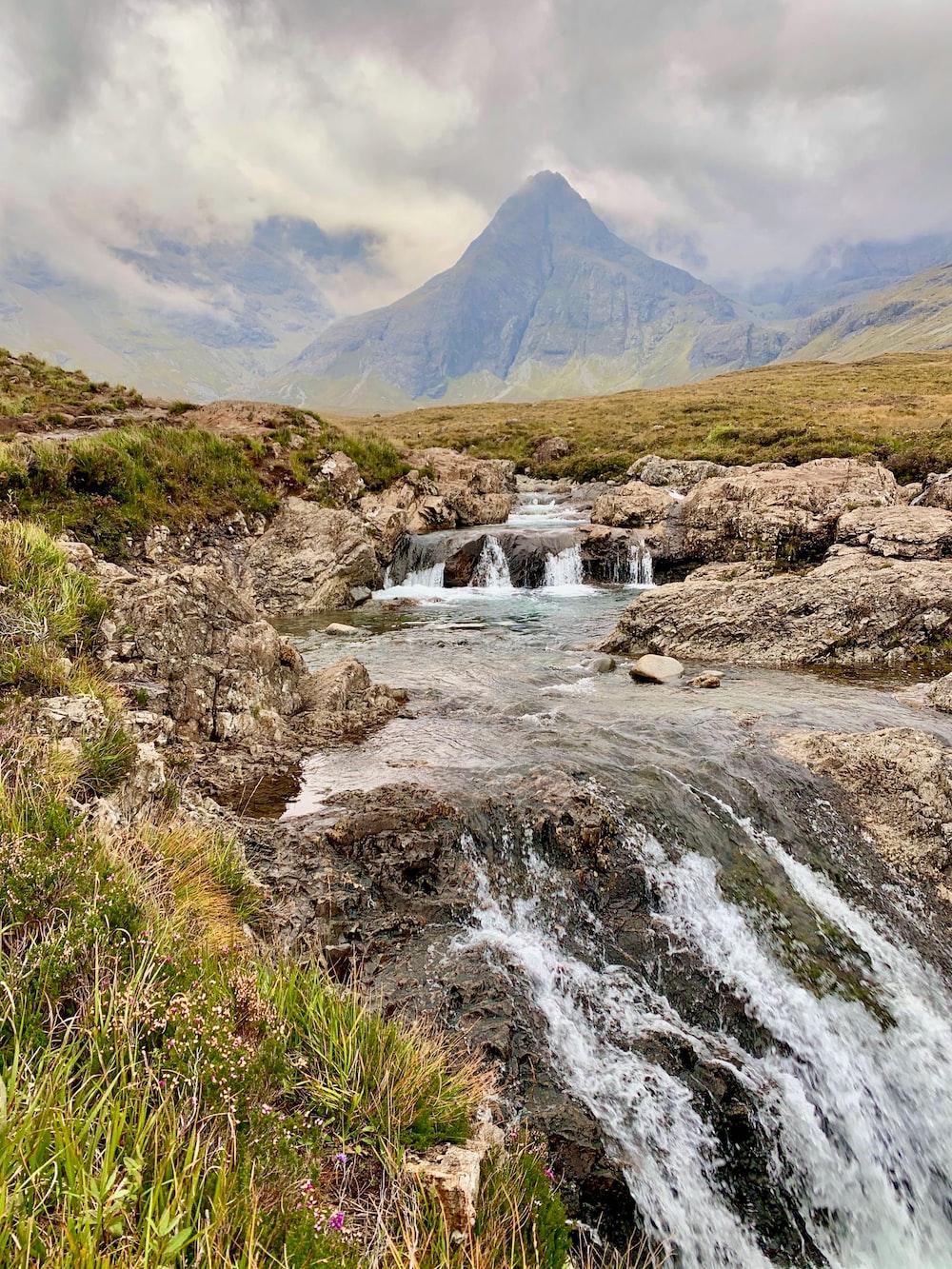 water falls near green mountain during daytime