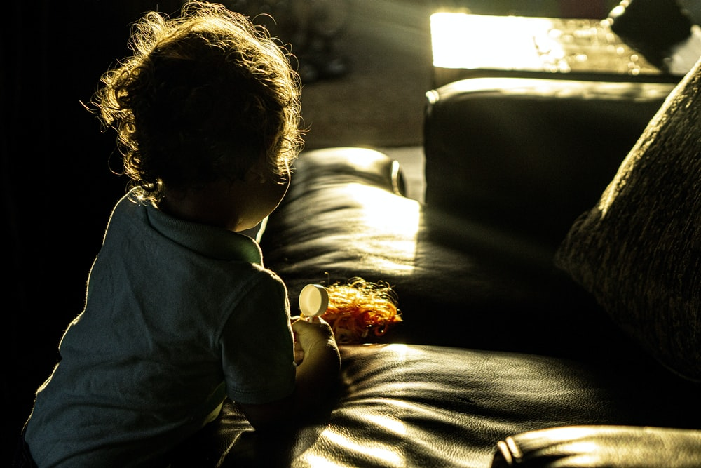 child in blue long sleeve shirt sitting on brown couch