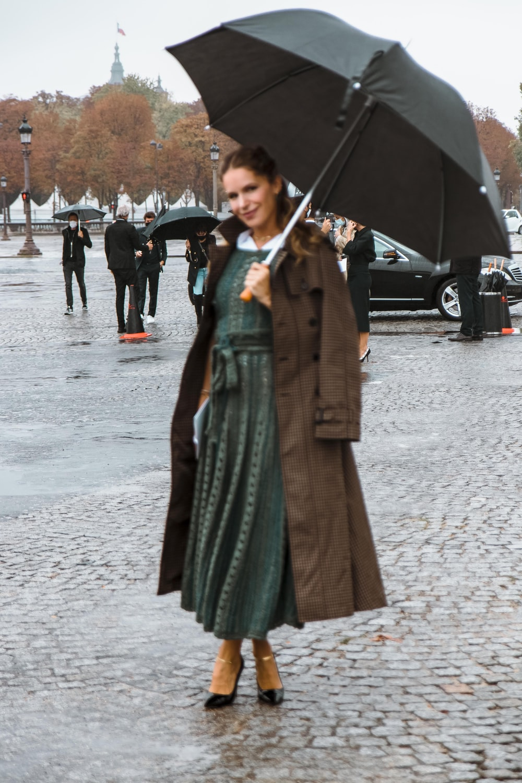 woman in green coat holding umbrella