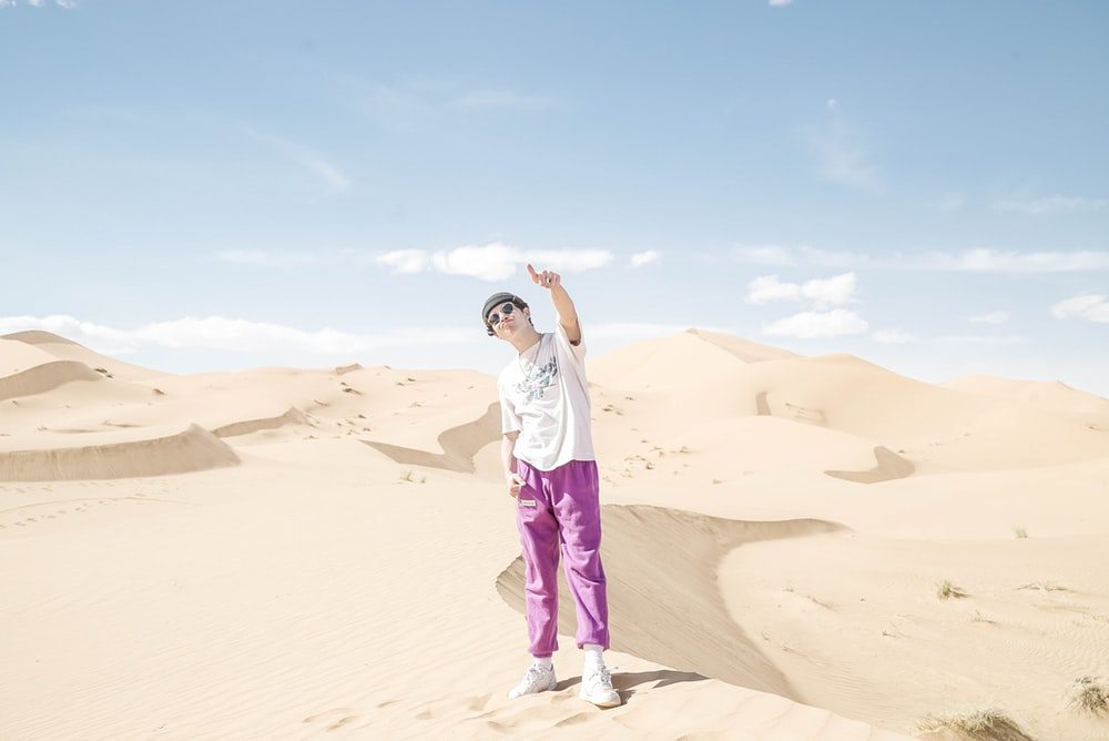 woman in white t-shirt and purple pants standing on brown sand during daytime