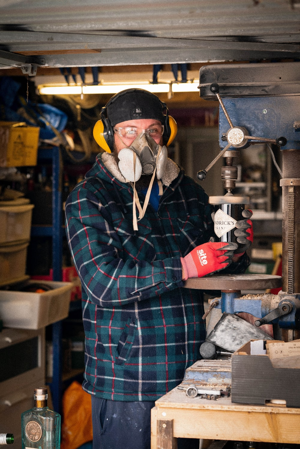 man in blue and red plaid dress shirt wearing yellow gas mask