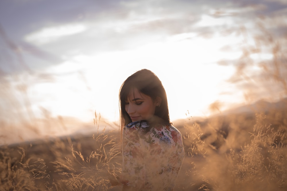 girl in white floral dress on brown grass field during daytime