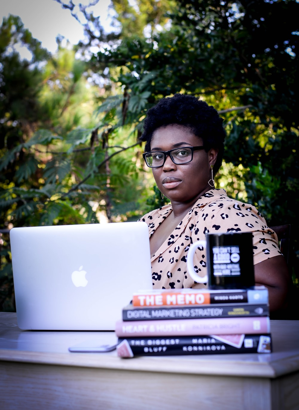 woman in white and black leopard print shirt using macbook