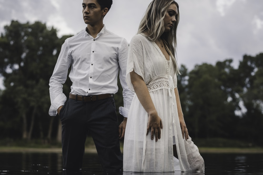 man in white button up shirt and black pants holding woman in white dress