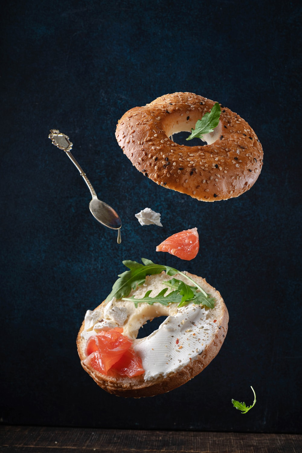 bread with sliced tomato and green vegetable on black textile