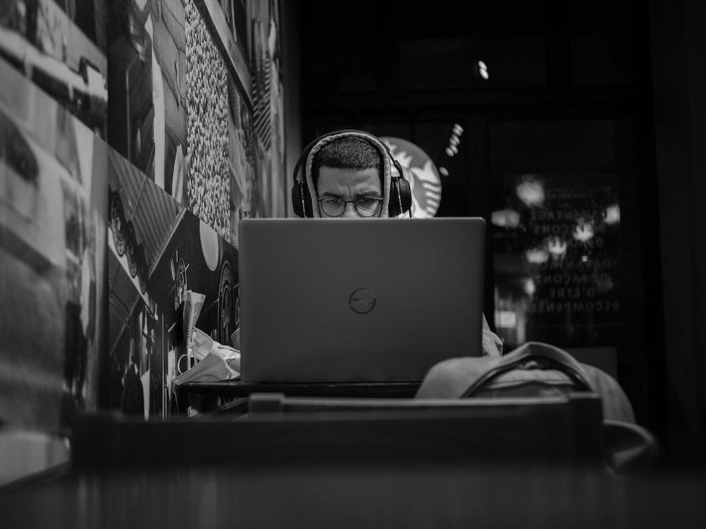 grayscale photo of man using macbook