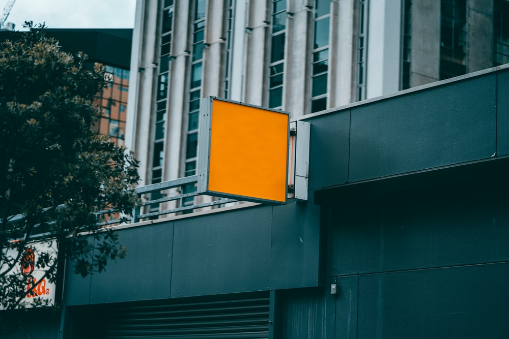 white and yellow basketball hoop on gray building