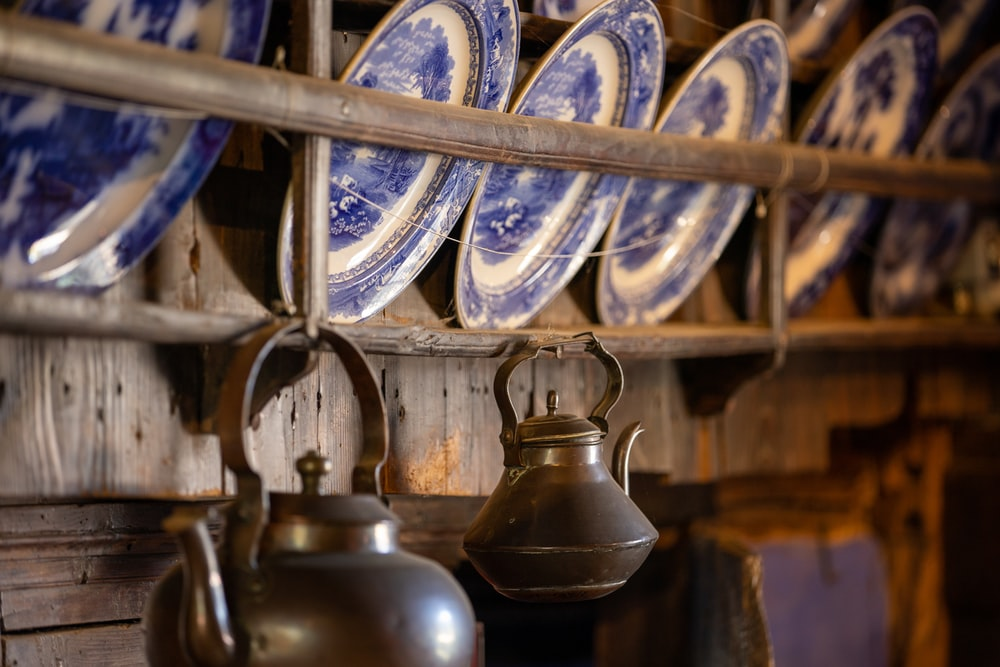 black and blue ceramic mugs on brown wooden rack