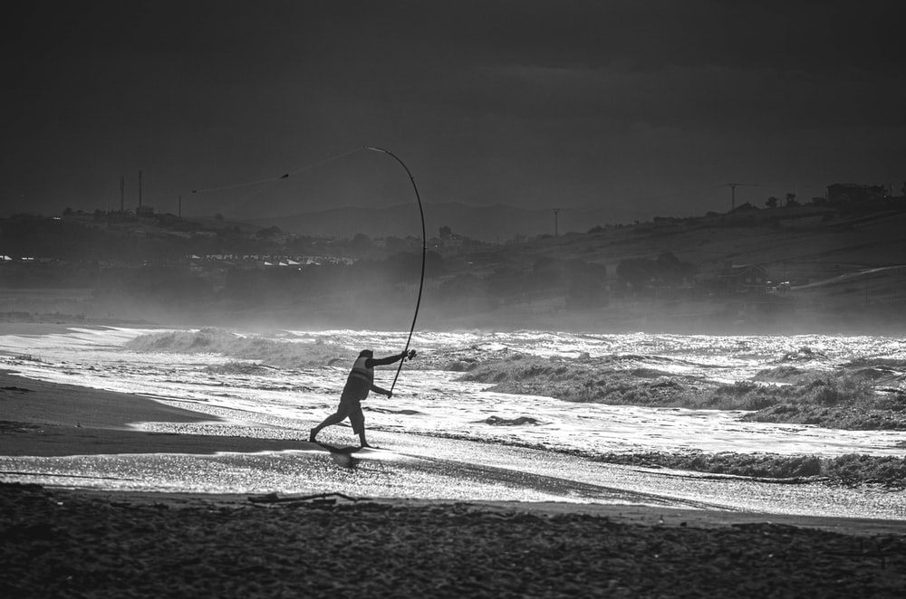 grayscale photo of person holding fishing rod walking on beach shore