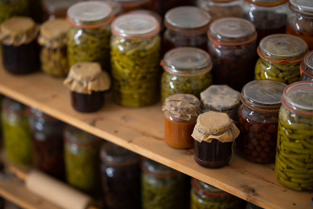 clear glass jars on brown wooden shelf