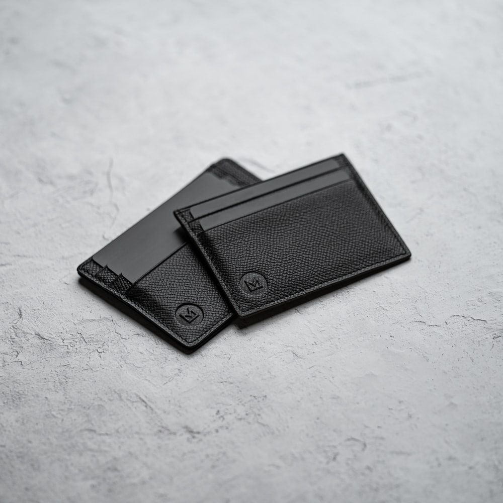 black leather bifold wallet on white surface