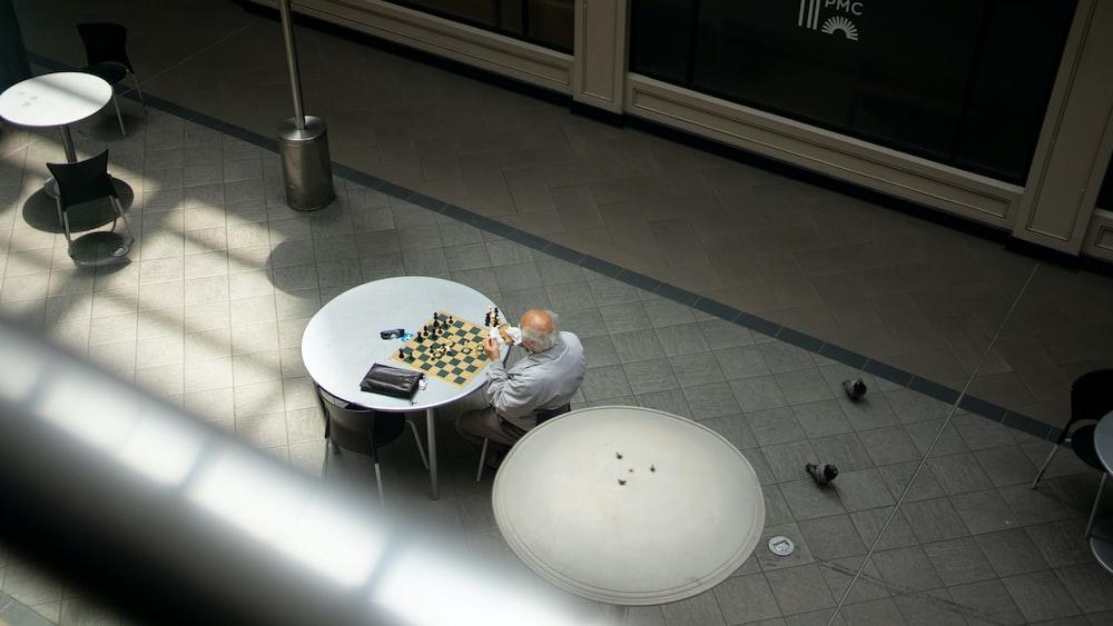 man in white dress shirt sitting on white round table