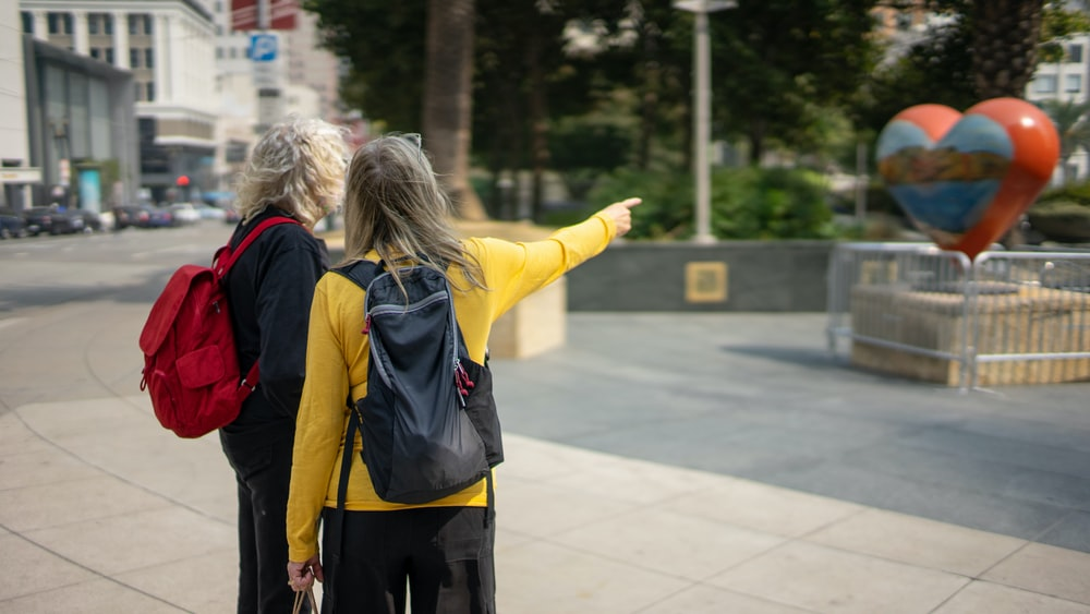 woman in yellow jacket and black backpack walking on sidewalk during daytime