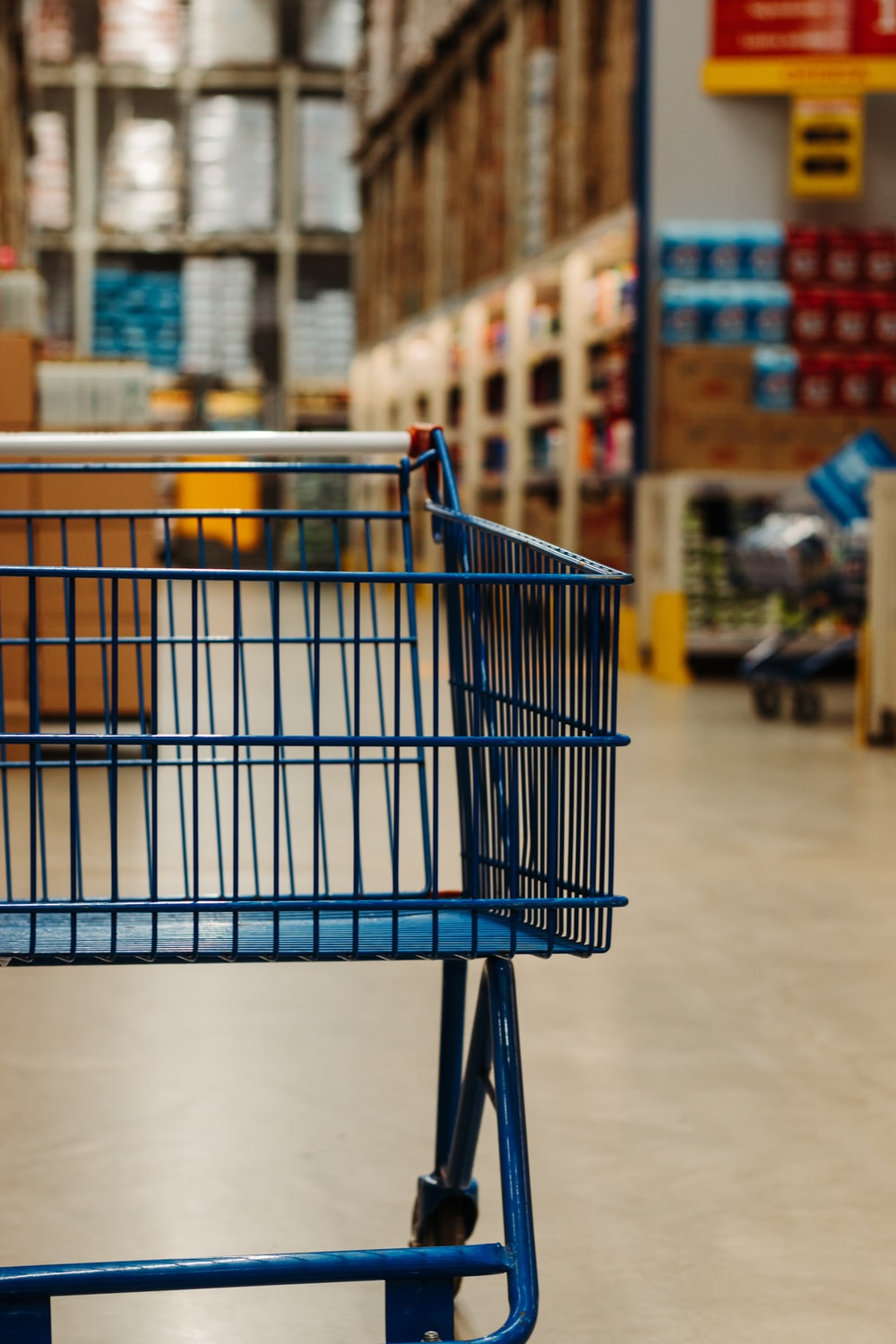 blue shopping cart on white floor