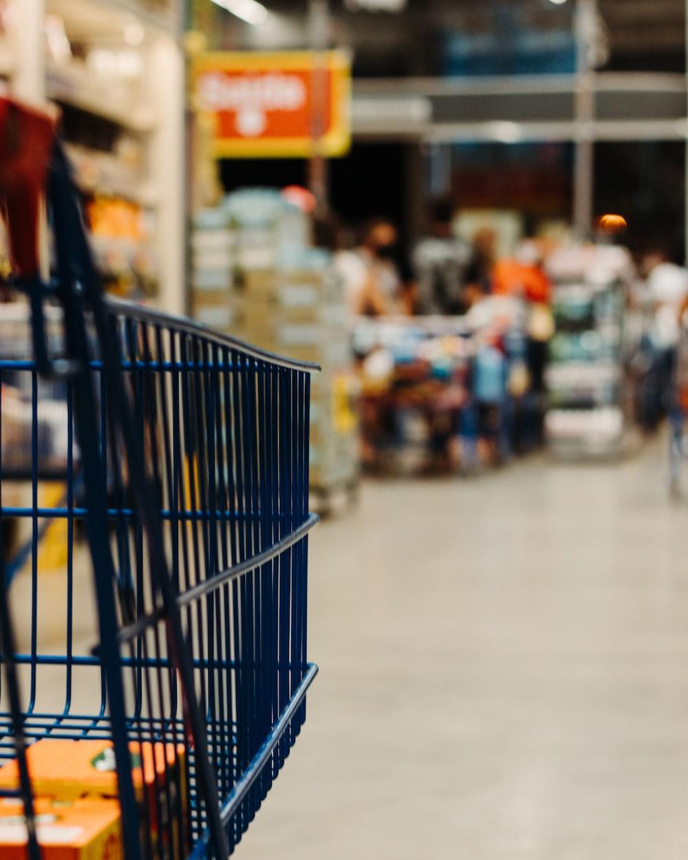 blue shopping cart on street during daytime