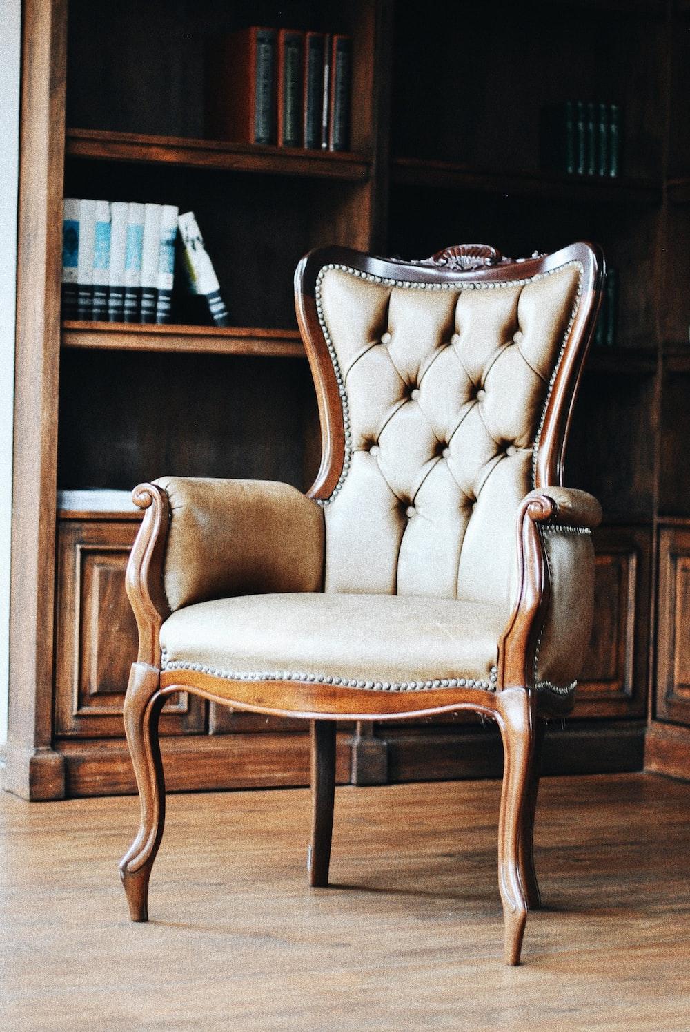 brown wooden framed beige padded armchair