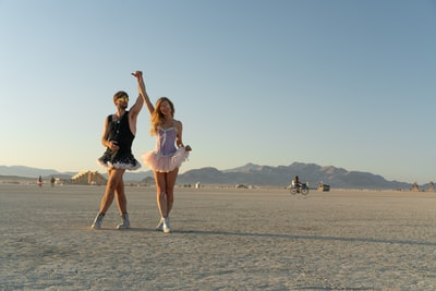 woman in pink dress running on gray sand during daytime burning man teams background