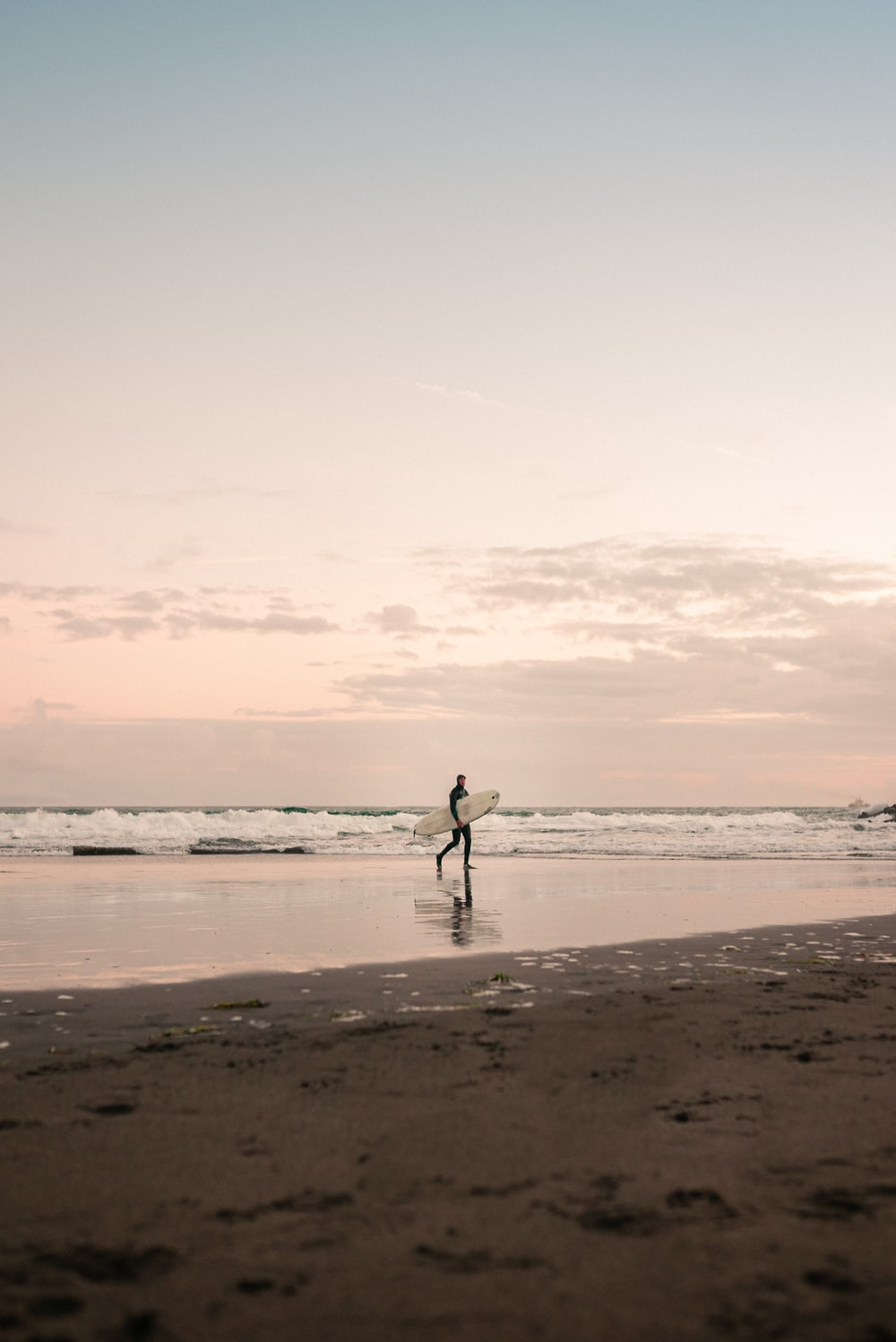 silhouette of man walking on beach during daytime
