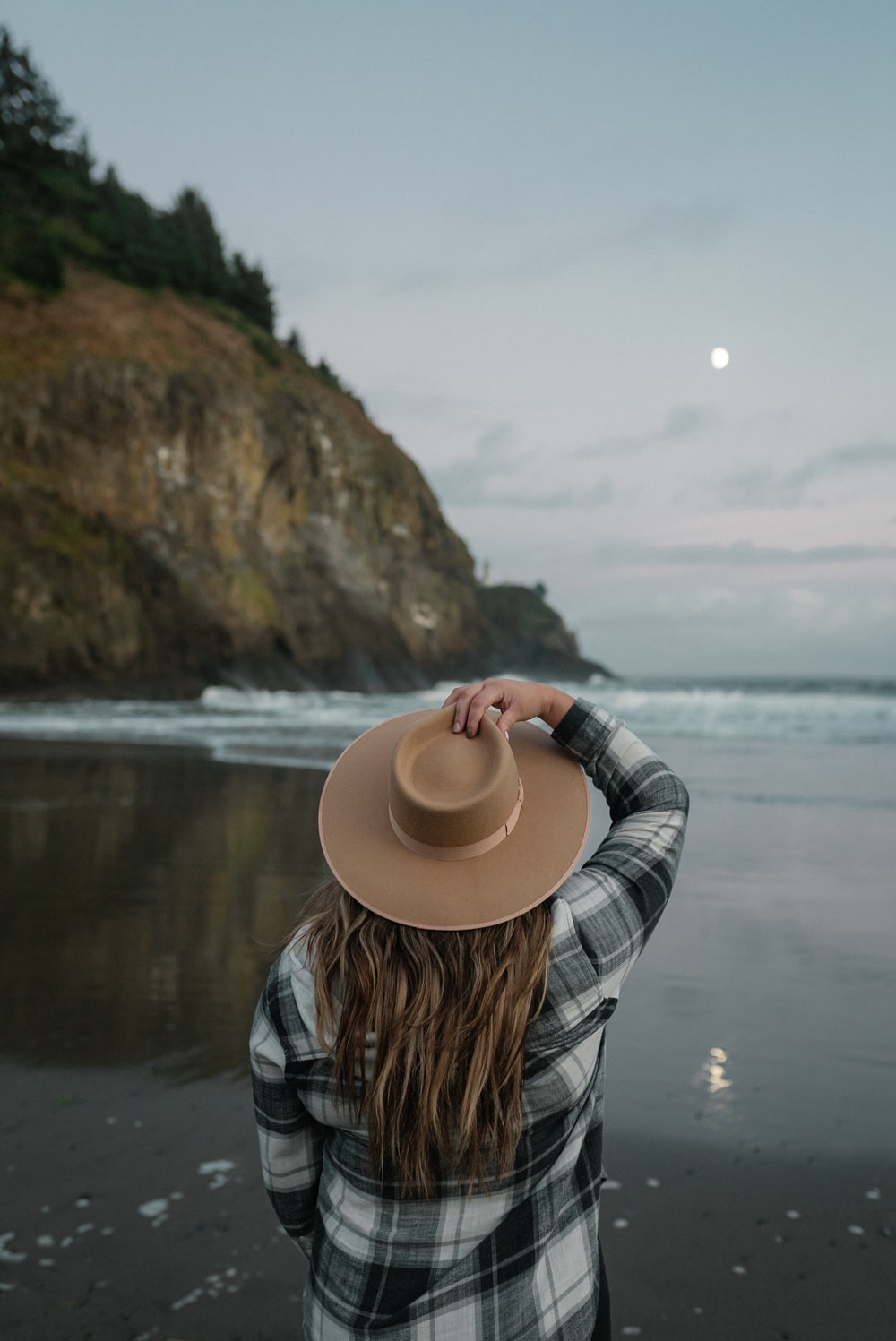 woman in blue and white plaid long sleeve shirt and beige hat standing near body of near on with near