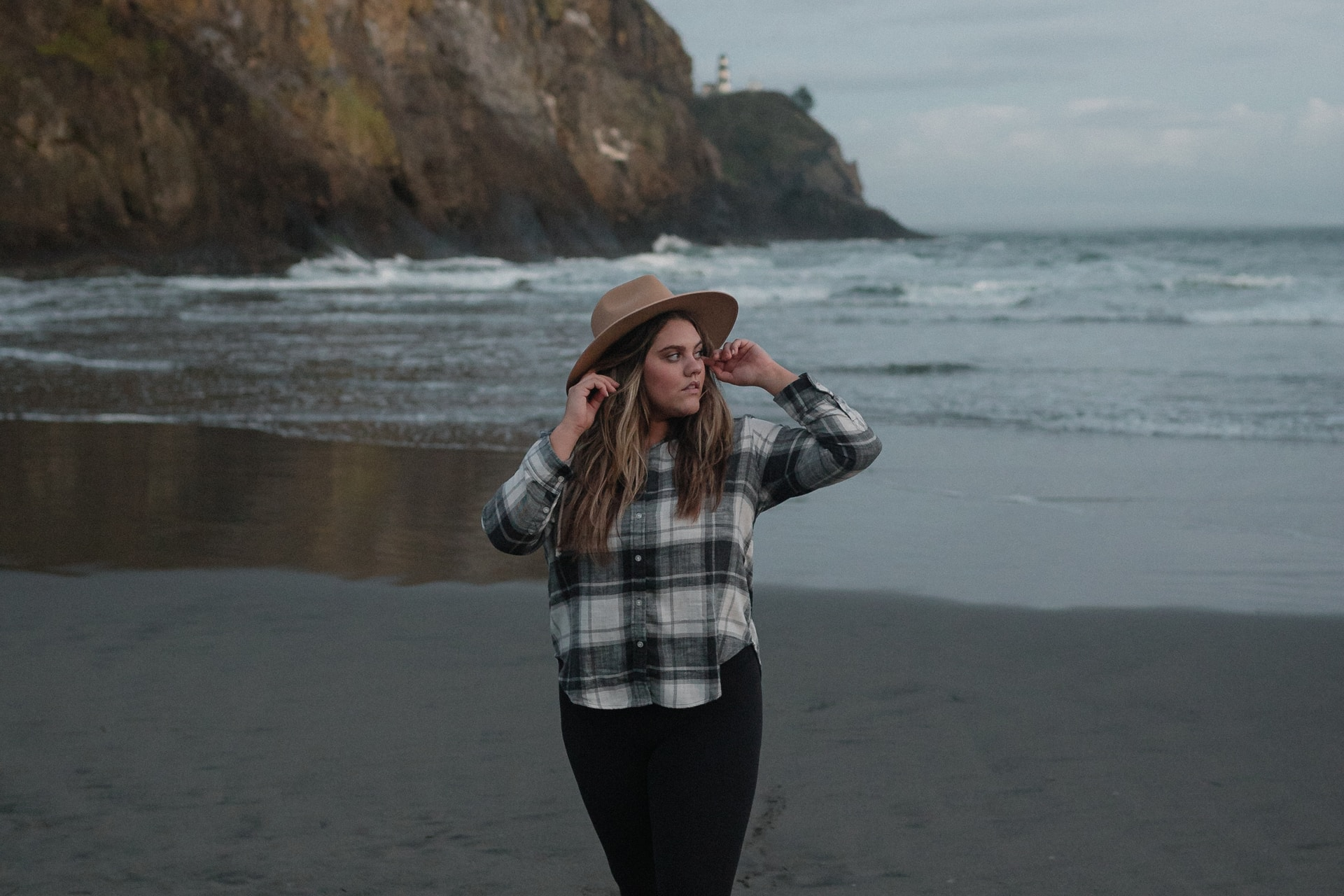 woman in black and white plaid long sleeve shirt standing on beach shore during daytime