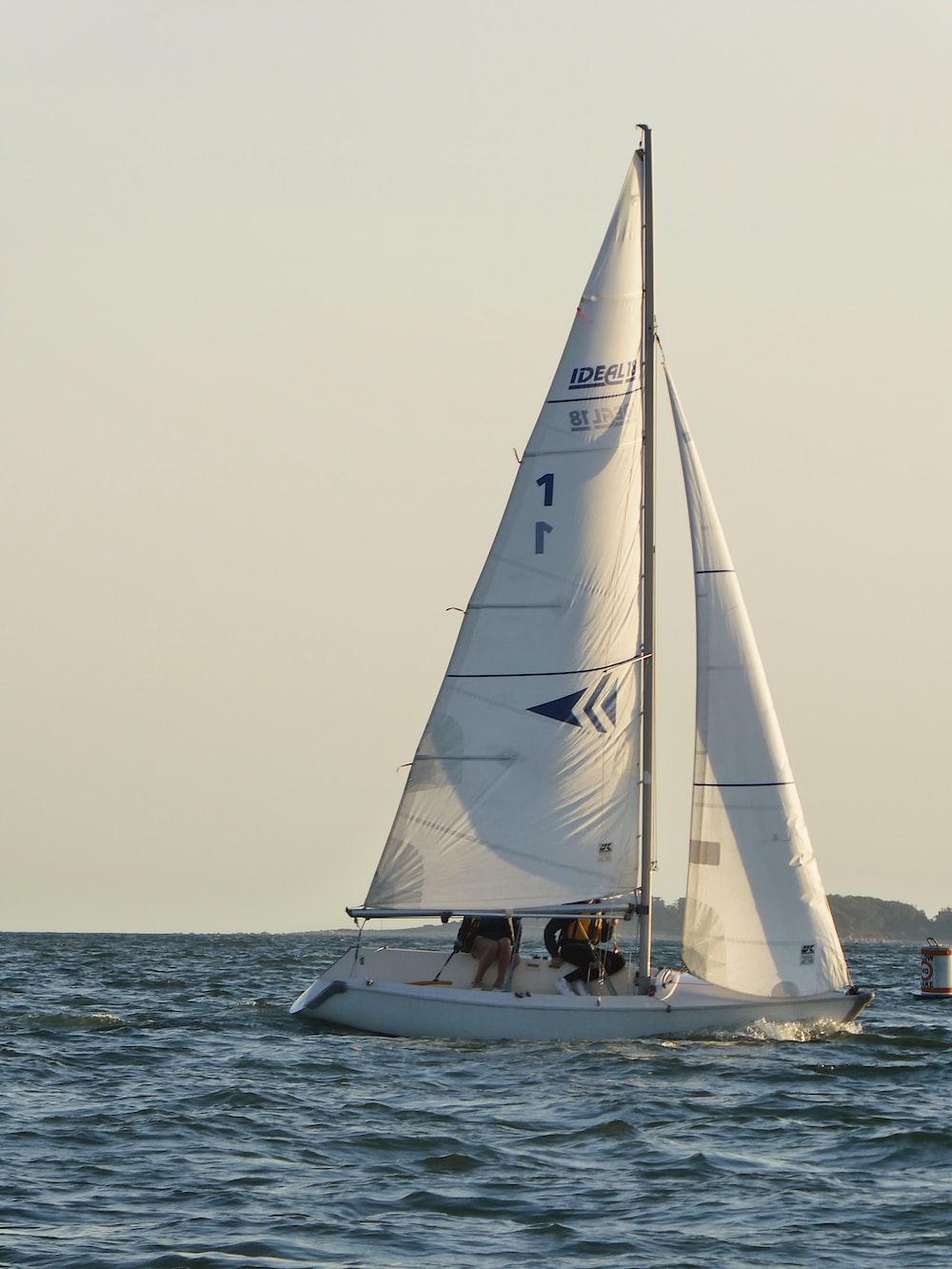 white sail boat on sea during daytime