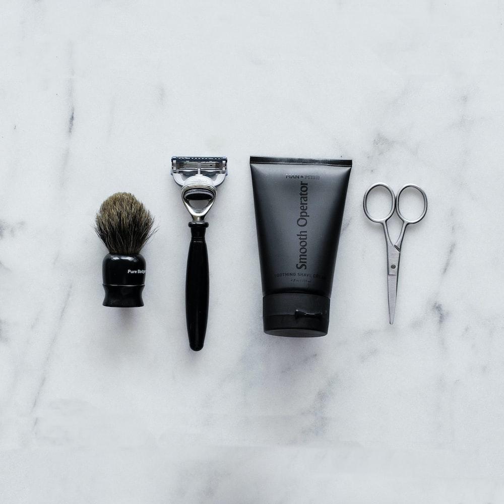 black and silver hair brush beside black soft tube