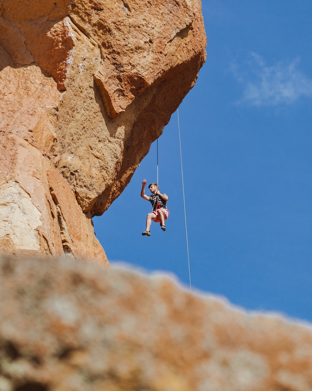man in black shirt and black shorts jumping on brown rock during daytime
