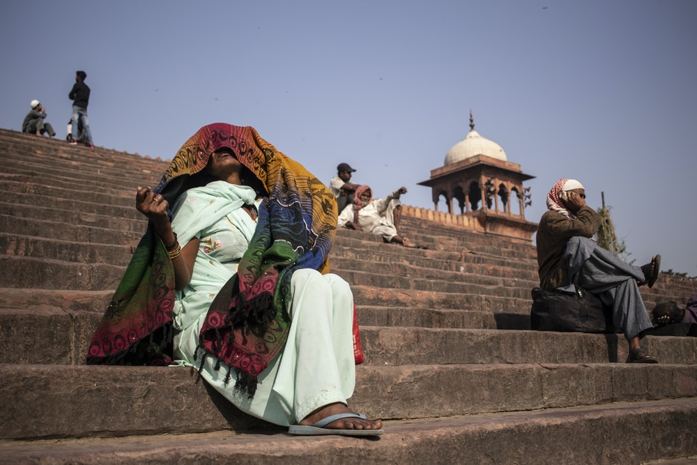 woman in green and red sari sitting on brown concrete stairs during daytime