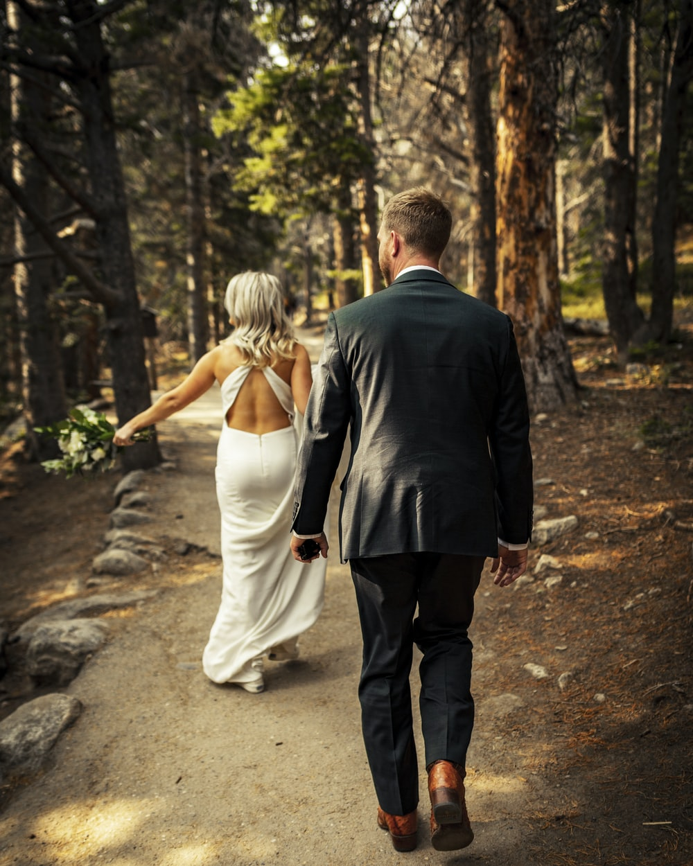 man in black suit jacket and woman in white dress walking on pathway during daytime