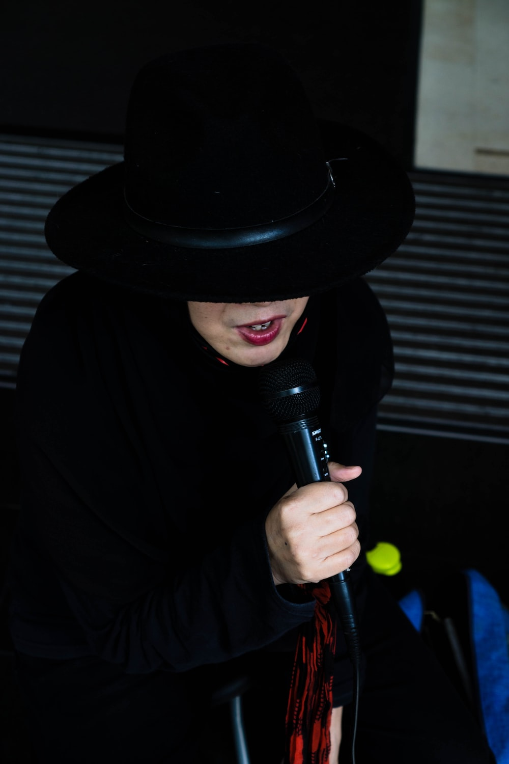 man in black hat holding microphone