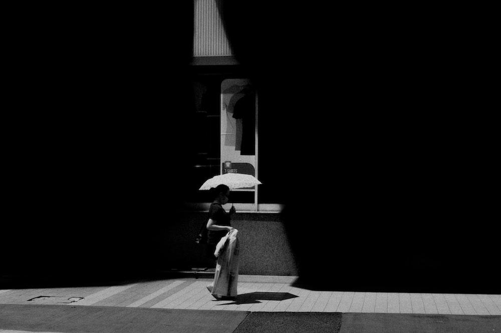 grayscale photo of woman in white dress walking on sidewalk