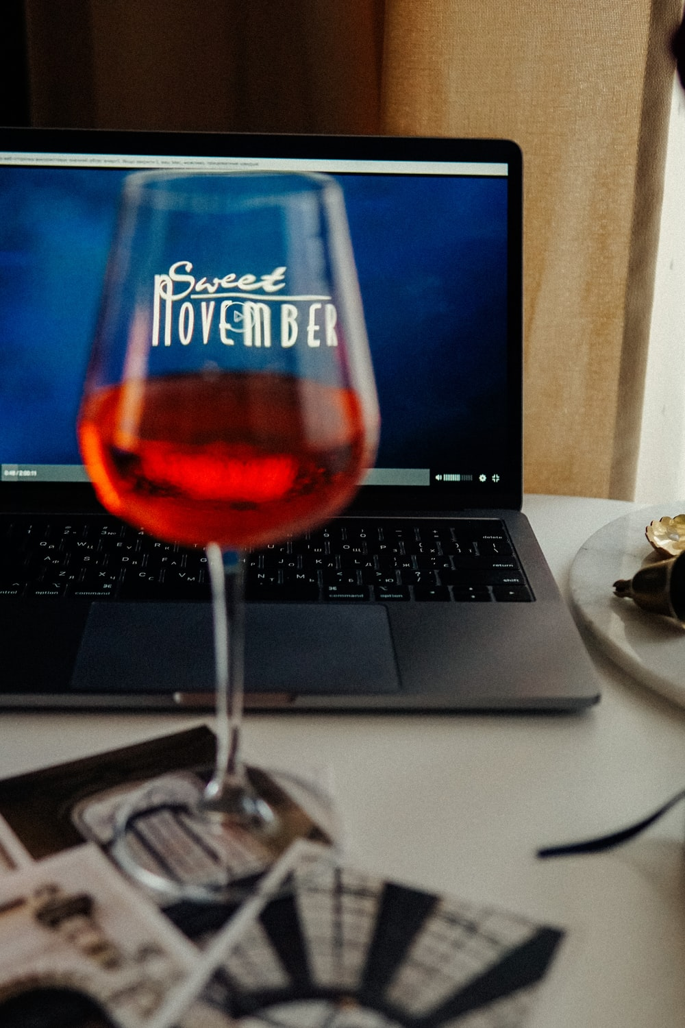 clear wine glass beside black and silver laptop computer