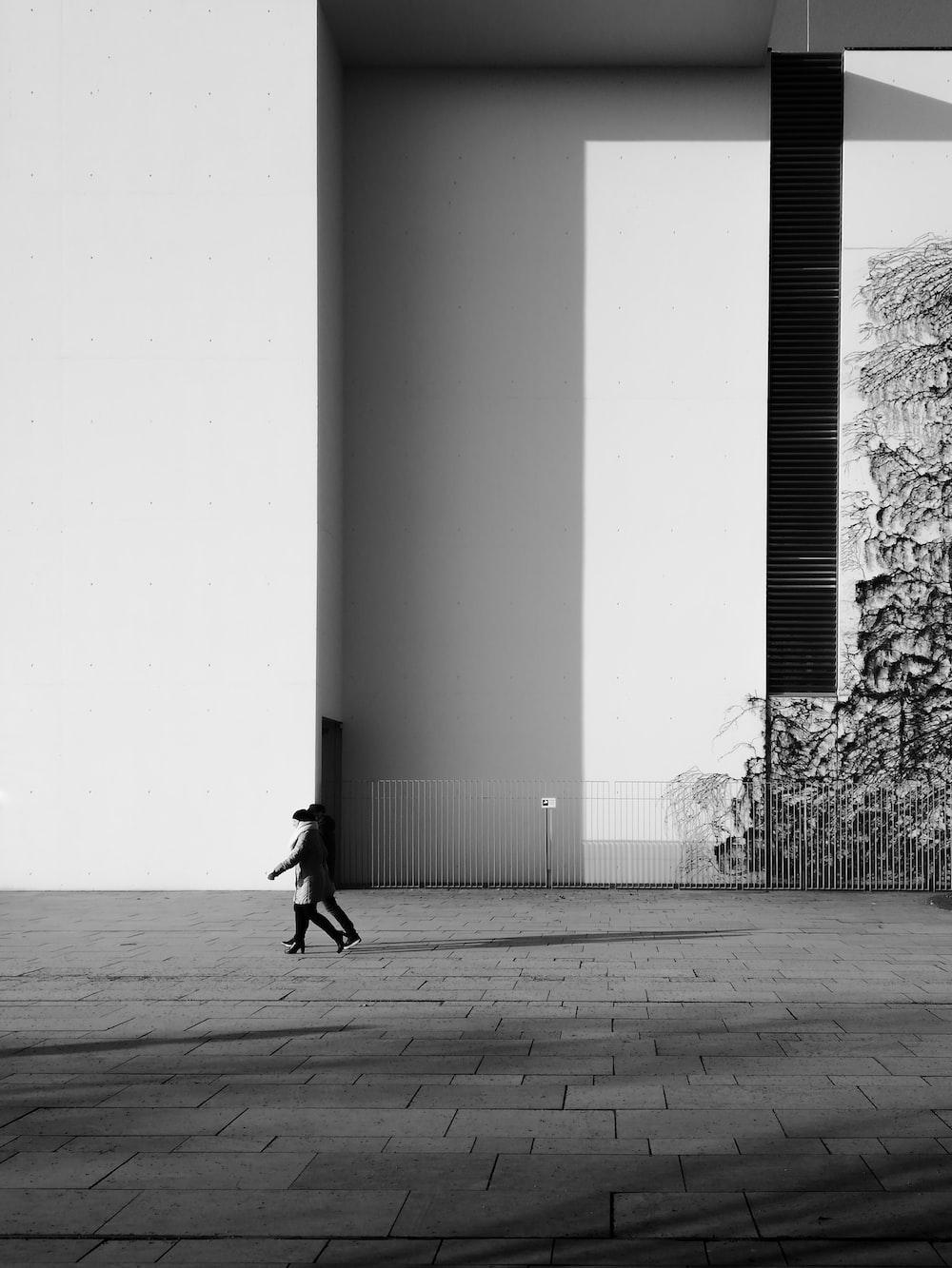 person walking on sidewalk near building