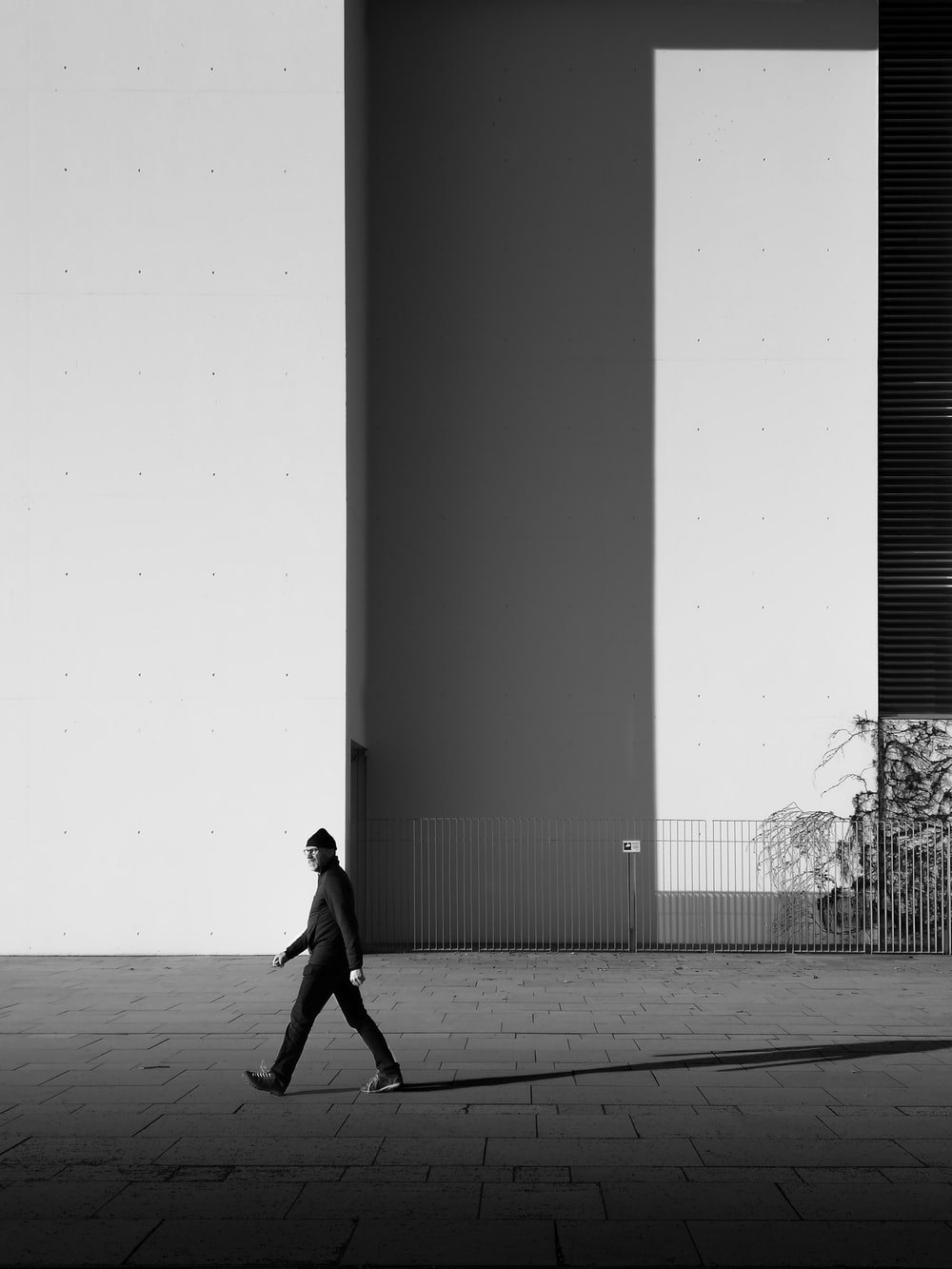 grayscale photo of woman walking on the street