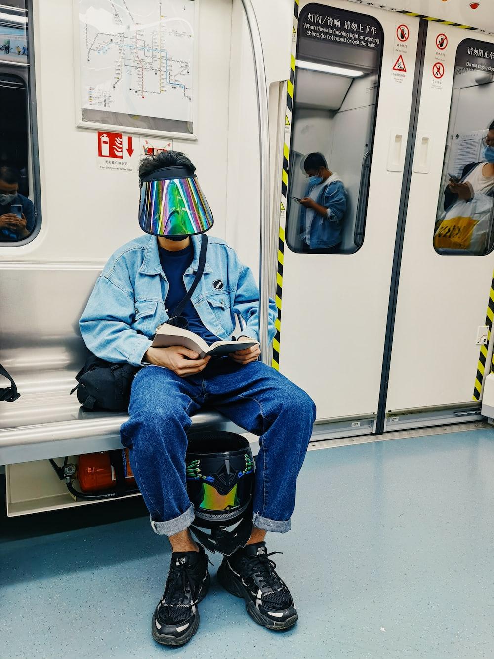 man in blue jacket sitting on train seat