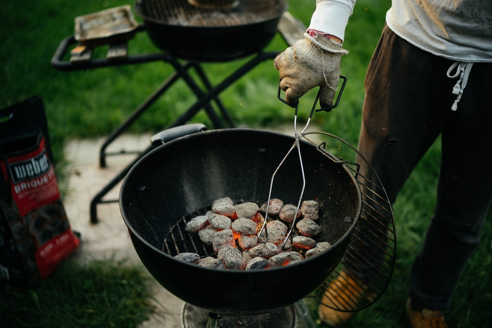 person cooking meat on black round pan