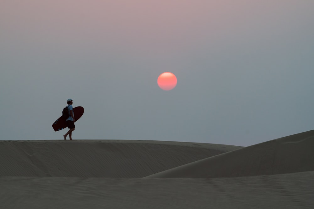 man in black jacket and pants walking on gray sand during sunset