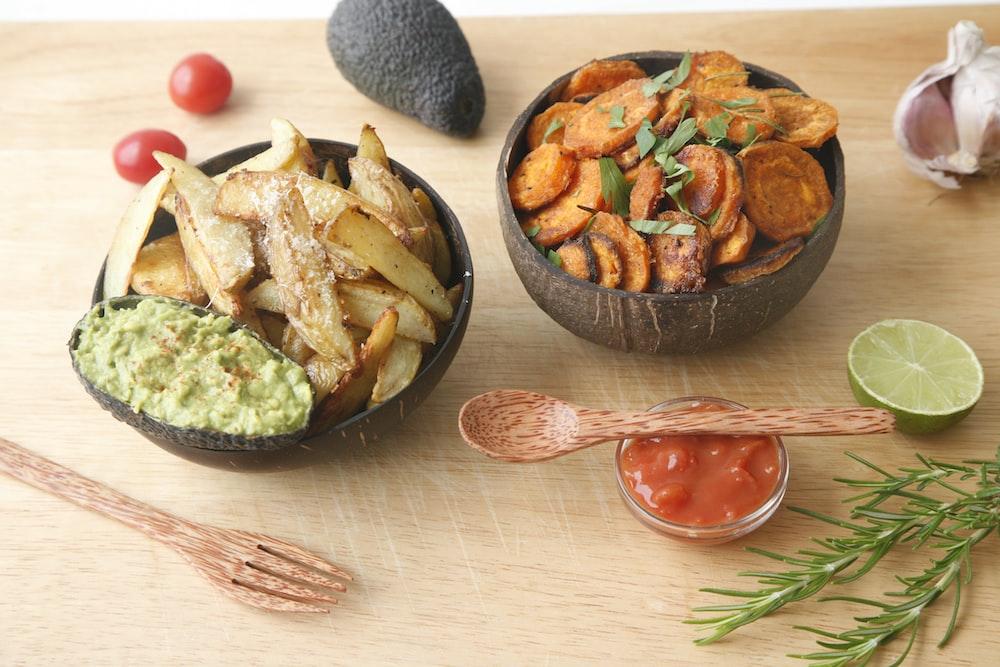 vegetable salad on black ceramic bowl beside brown wooden spoon
