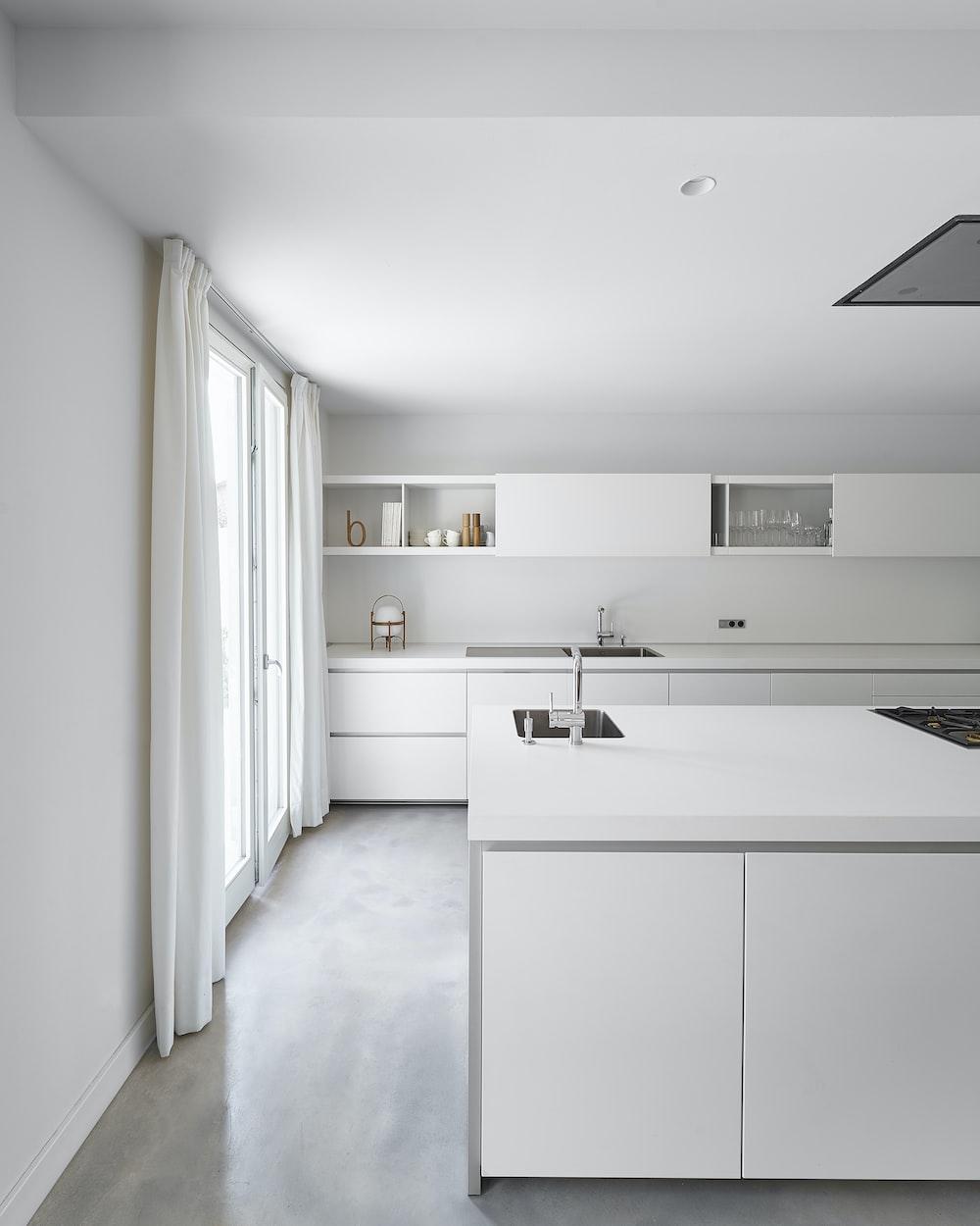 white wooden kitchen cabinet near white wall