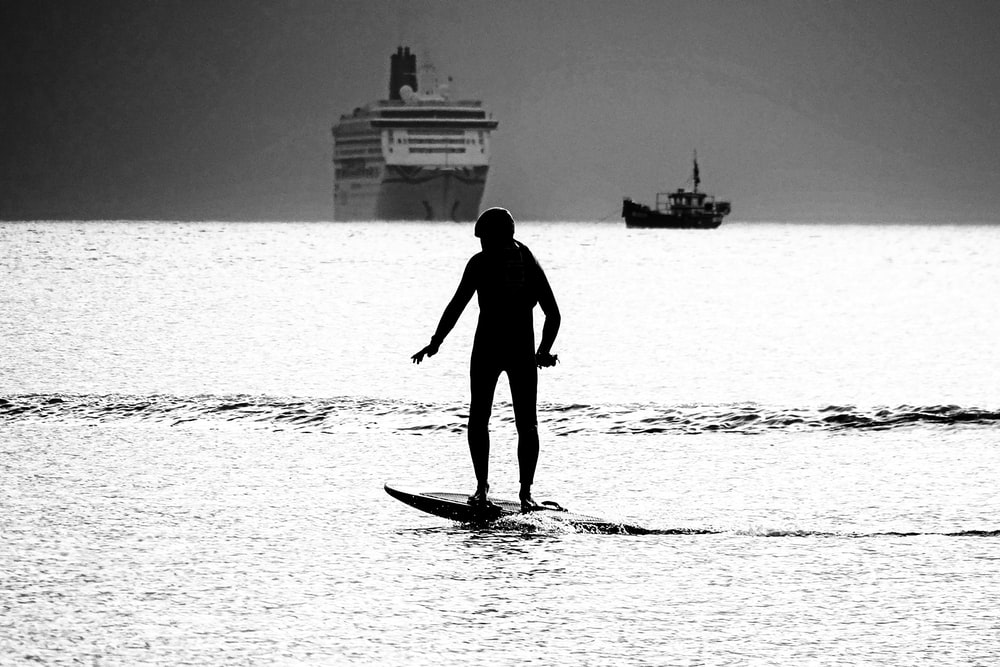 silhouette of man in surfboard on sea during daytime