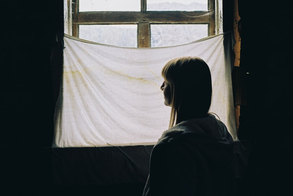 woman in black shirt standing in front of window
