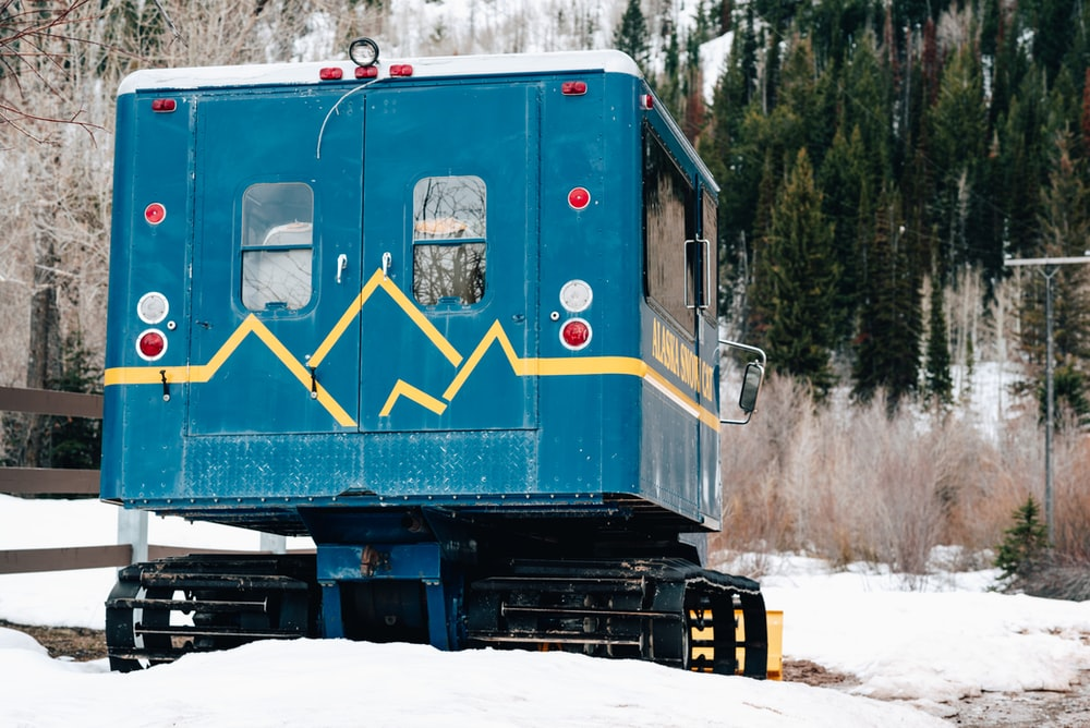 blue and yellow train on snow covered ground during daytime