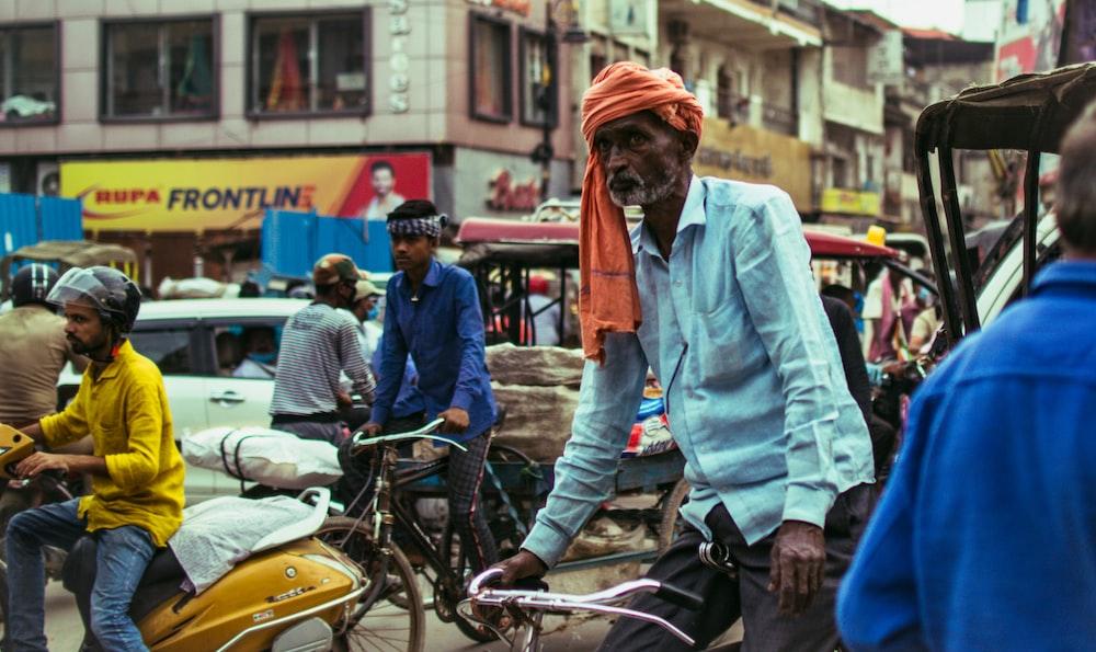 man in blue denim jacket and orange knit cap riding on yellow motorcycle during daytime