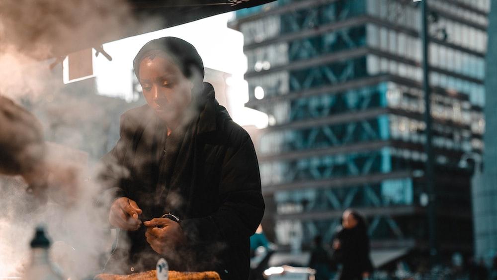 man in black leather jacket smoking cigarette