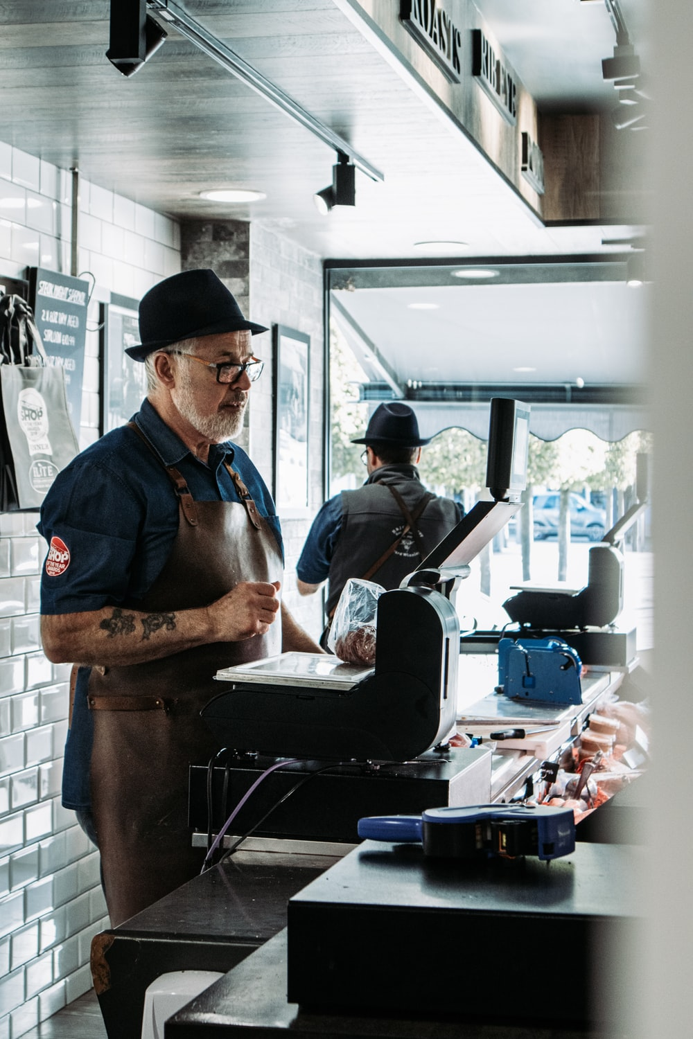 man in blue vest and black apron cooking