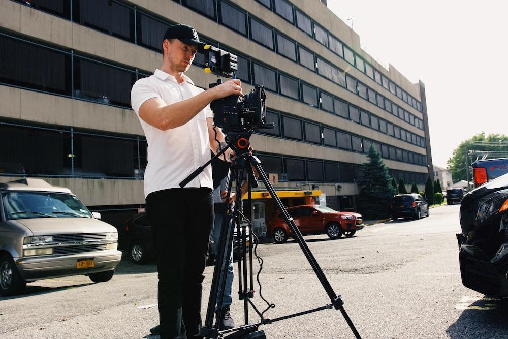 man in white t-shirt and black pants holding black dslr camera
