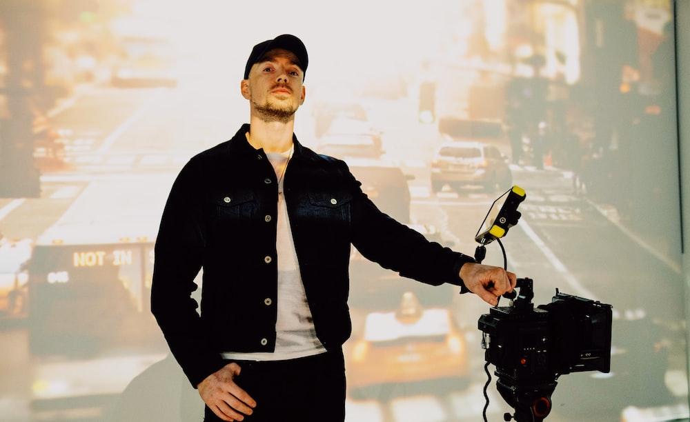 man in black button up jacket holding black dslr camera